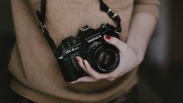 femme avec appareil photo autour du cou